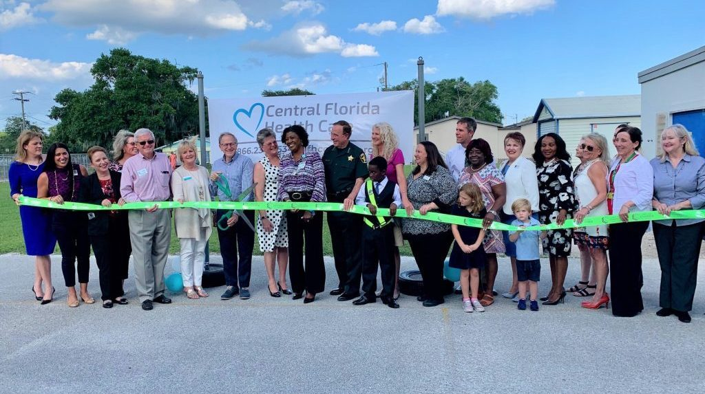 District and community members cutting a ribbon for the grand opening of the clinic at crystal lake elementary